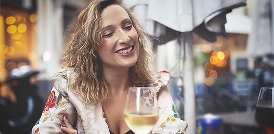 A single older woman drinking white wine