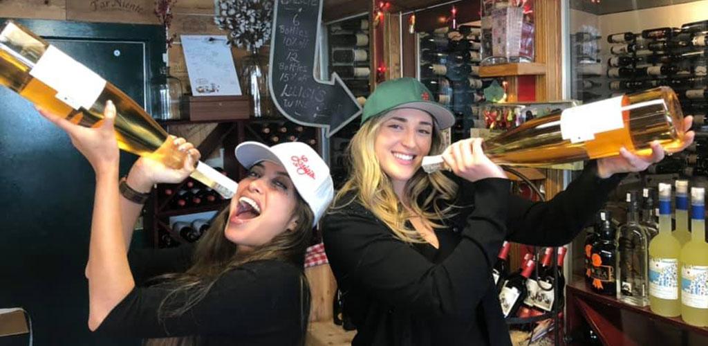 Women holding huge bottles of champagne at Luigi's Restaurant