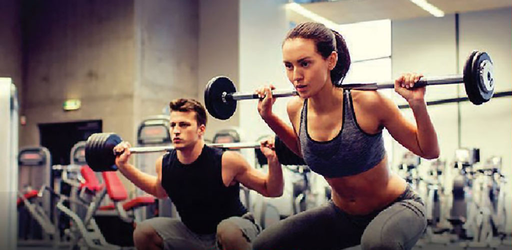 A man and a woman lifting weights at Titans Gym