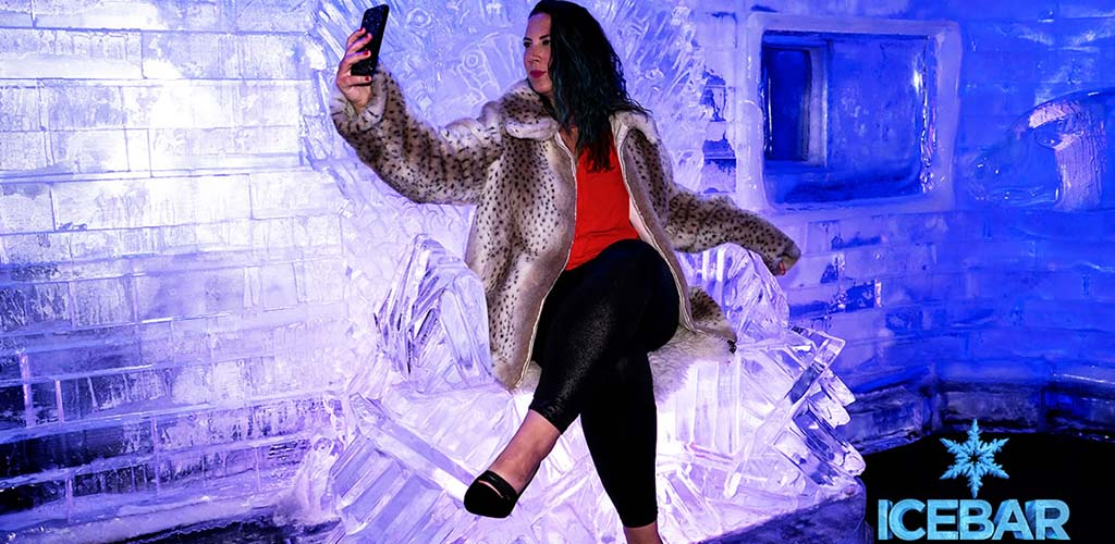 A mature woman posing on the frozen thrones at Ice Bar Orlando