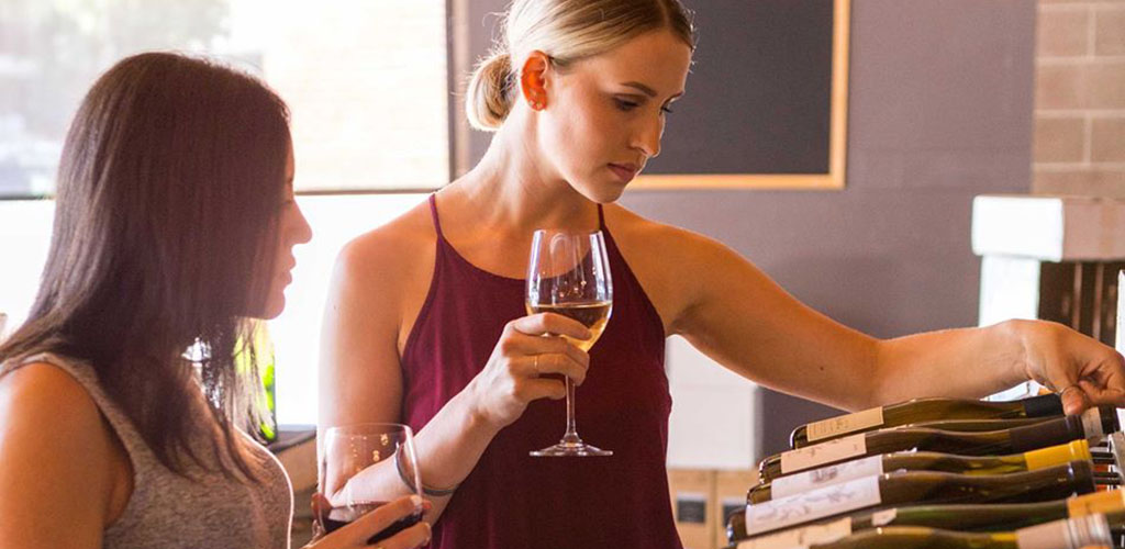 Women selecting different vintages at 58 Degrees and Holding Co.