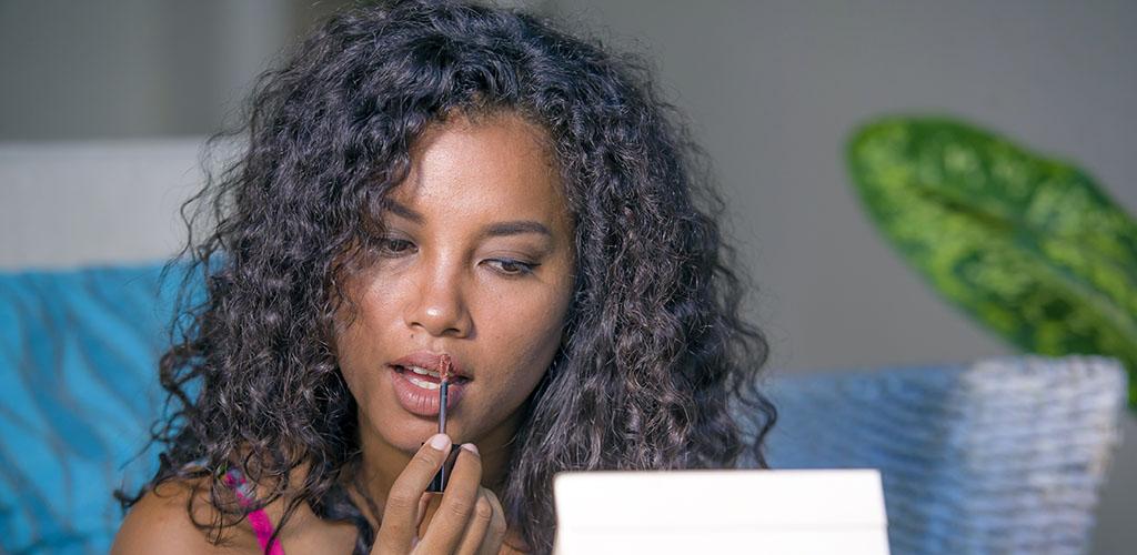 A beautiful woman applying lip gloss