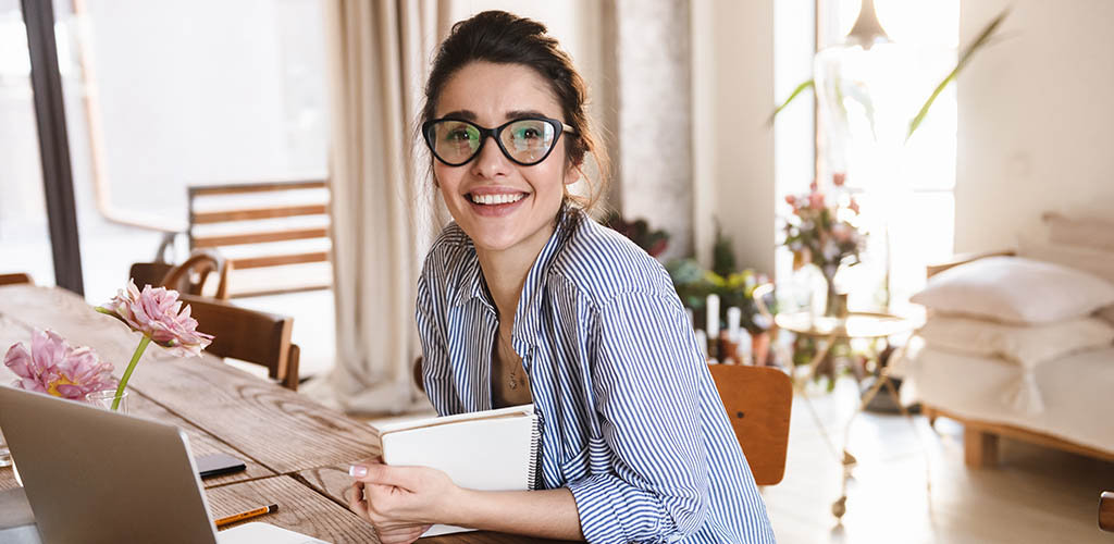 A woman with glasses working from home