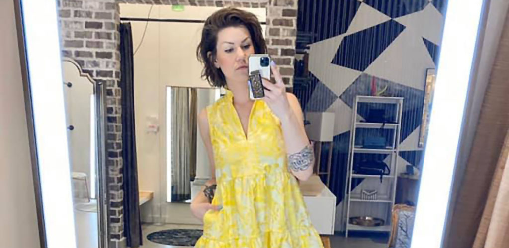 A woman in a yellow dress taking a mirror selfie at Galleria Edina