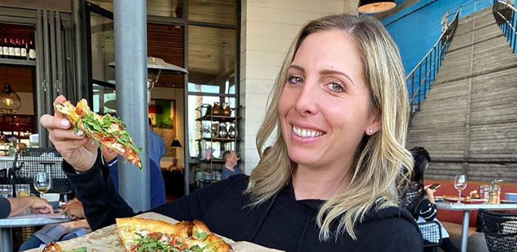 A woman enjoying her pizza from North Italia