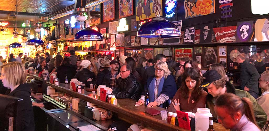 People crowding near the bar at Robert's Western World