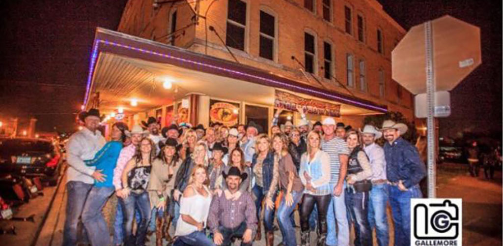 Group of cowboys and cowgirls outside of Rodeo Exchange Club