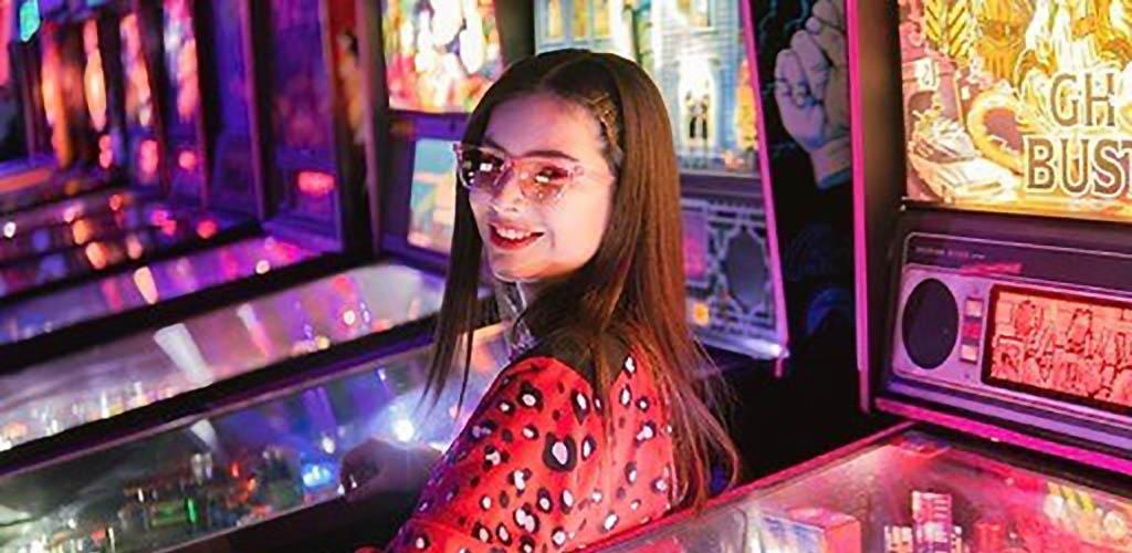 Woman smiling by pinball machine at Rubiks Arcade Bar
