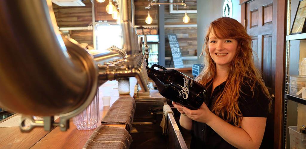 A beautiful woman bottling beer from Blackstone Brewpub