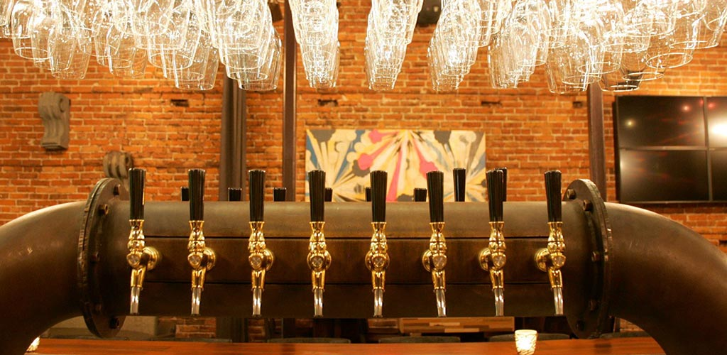 The gold beer taps at District against a rustic brick background