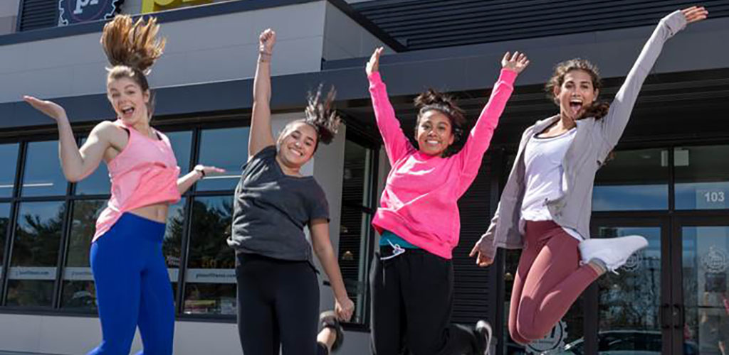 Women in a jump shot in front of Planet Fitness Gym