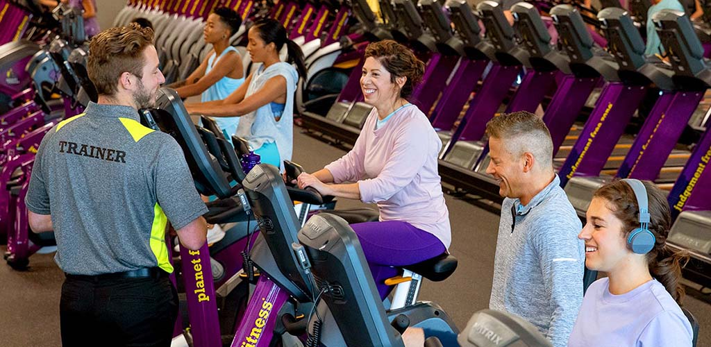 Women working out on stationary bikes at Planet Fitness