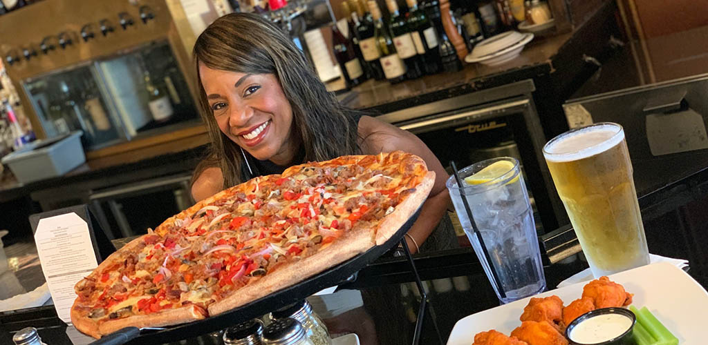 A woman with a giant pizza from Red White & Brew