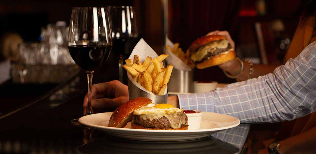 Burger with a side of fries and wine from The Capital Grille
