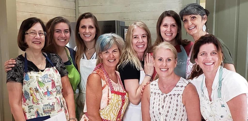 A group photo of mature women who attended a class at The Culinary Cottage