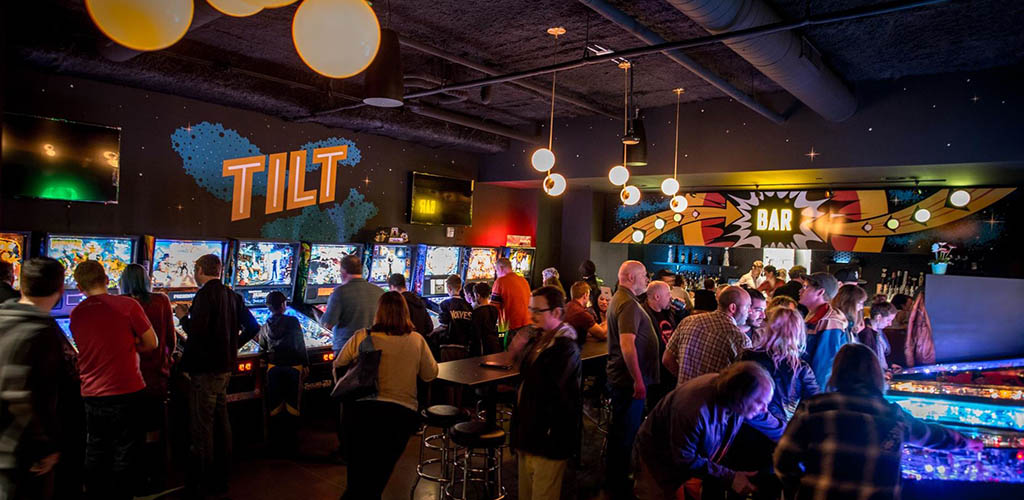 People playing arcade games and drinking at Tilt