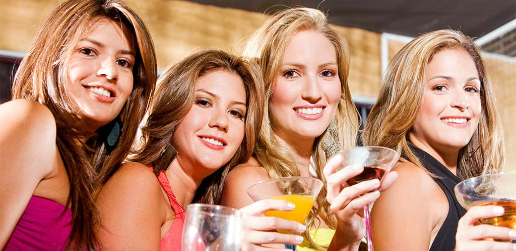 Four beautiful women drinking cocktails