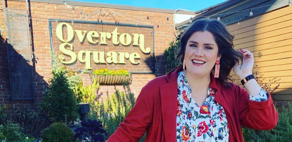 A voluptuous woman posing in front of Overton Square