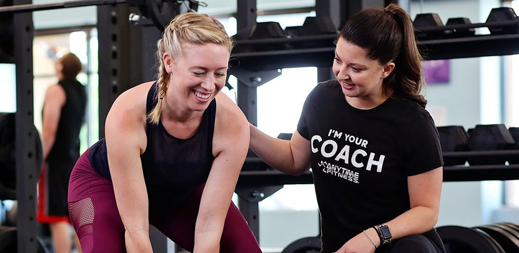 A mature woman working out with a trainer at Anytime Fitness