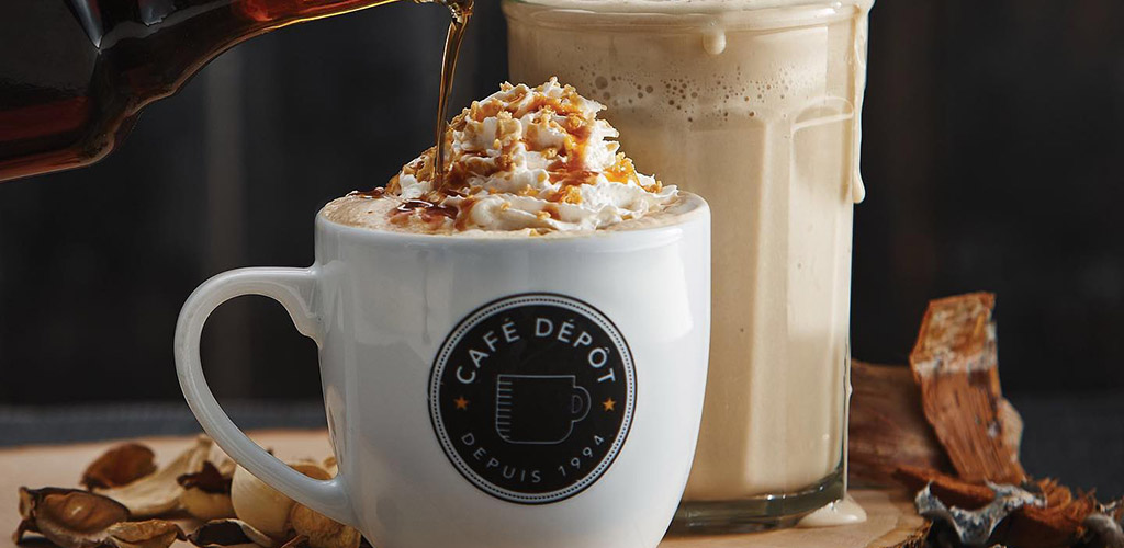 A latte topped with whipped cream from Cafe Depot