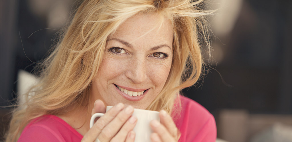 A beautiful blonde woman holding a cup of coffee