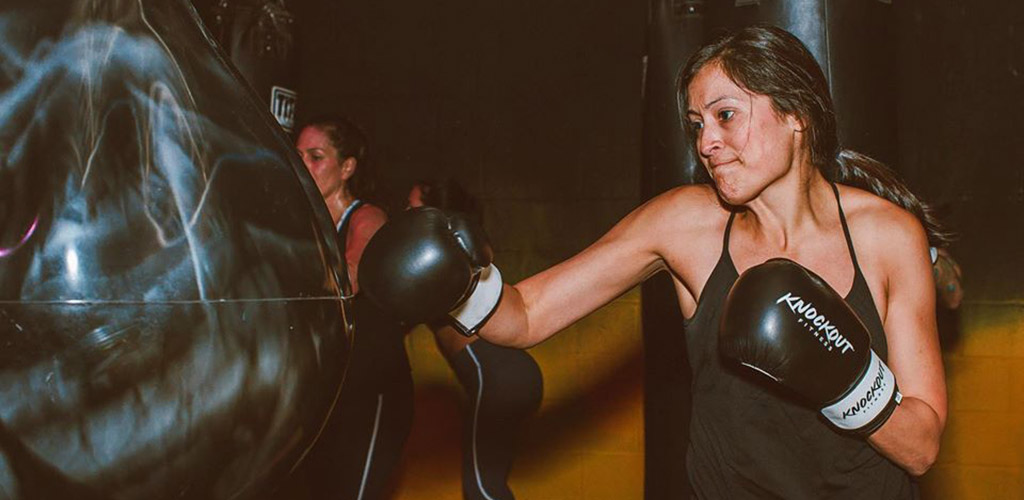 A fit woman boxing at The Knockout Fitness