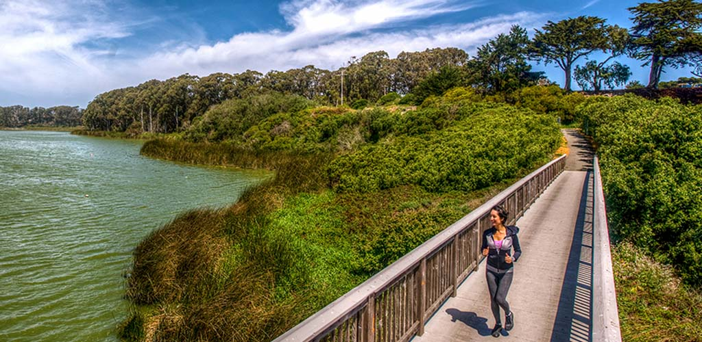 A woman jogging on the bridge at Lake Merced Park