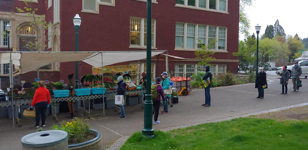 A few people buying goods at Portland Farmer's Market
