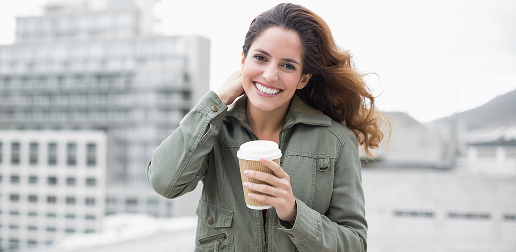 A woman enjoying her coffee while enjoying the view of the city
