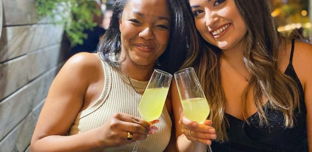 Classy Oakland cougars toasting drinks at Oeste Rooftop Bar