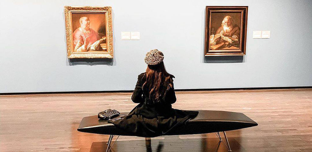 A woman admiring works by Pieter Lastman at The Art Gallery of Alberta