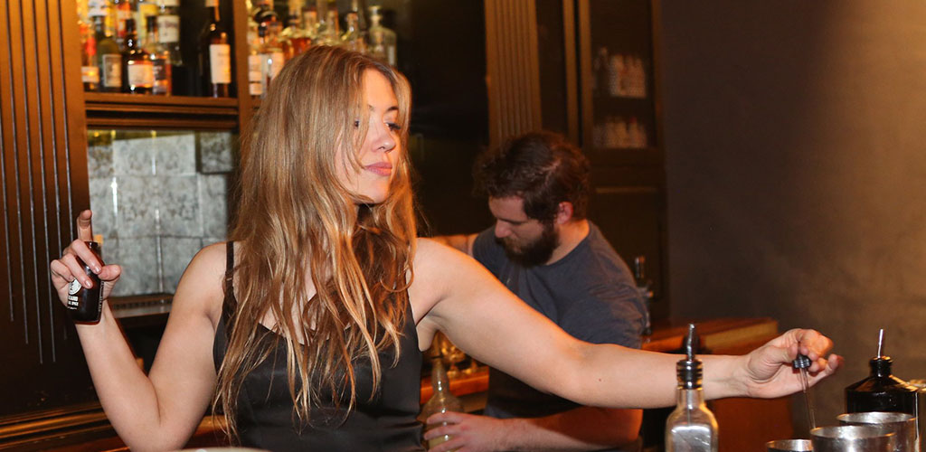 A beautiful woman mixing drinks at Bitter and Twisted