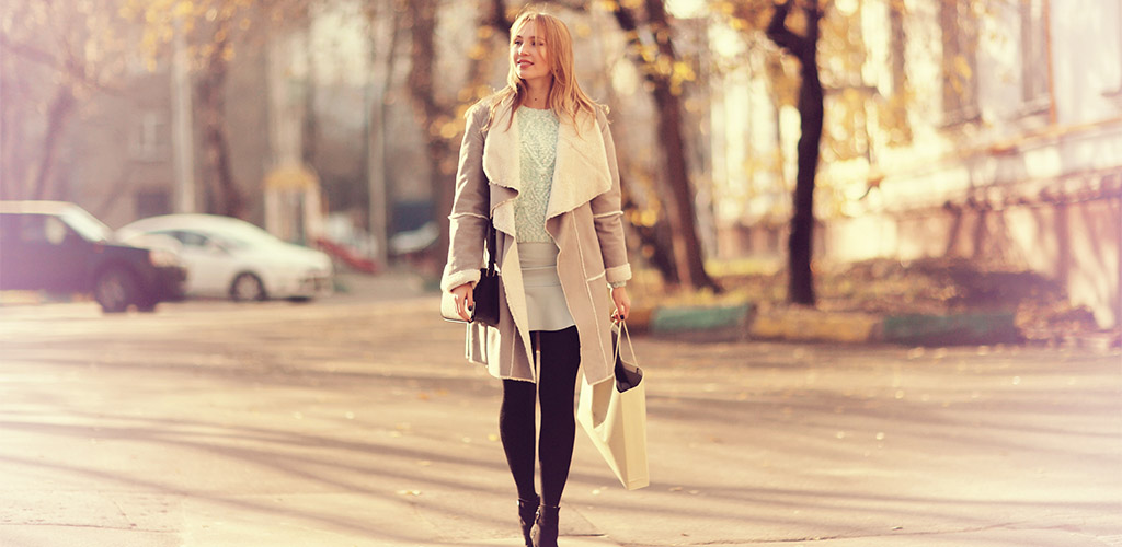 A beautiful woman in a coat walking around town