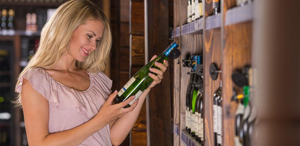 Blonde woman examining wine bottle