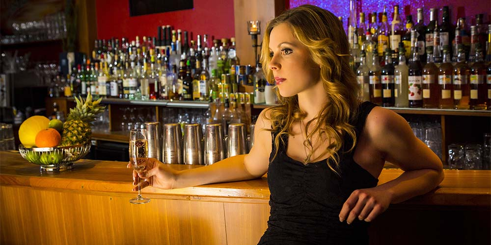 A beautiful woman drinking champagne at a bar