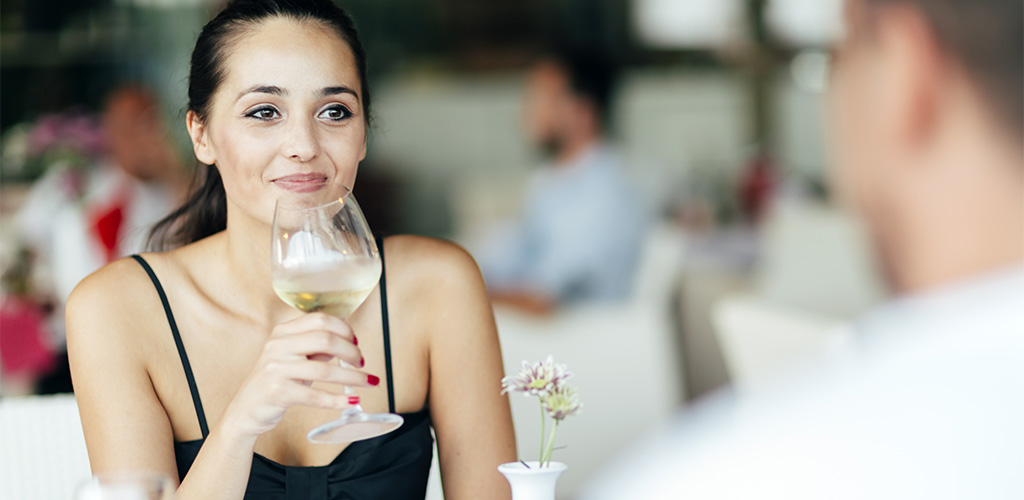 A beautiful cougar in San Diego drinking wine while on a date