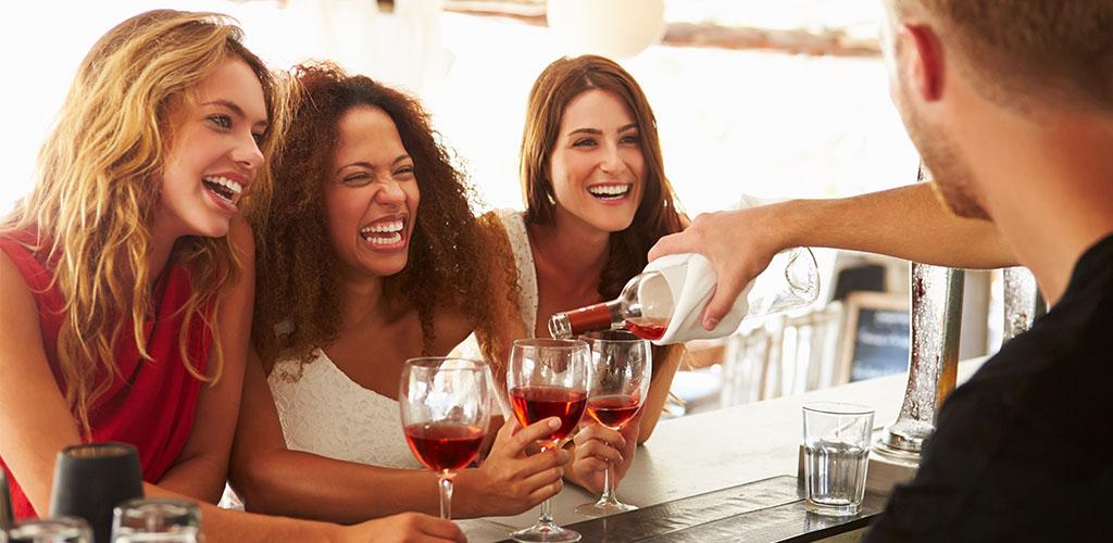 Fun loving MILFs in Virginia Beach drinking wine at a beach side bar