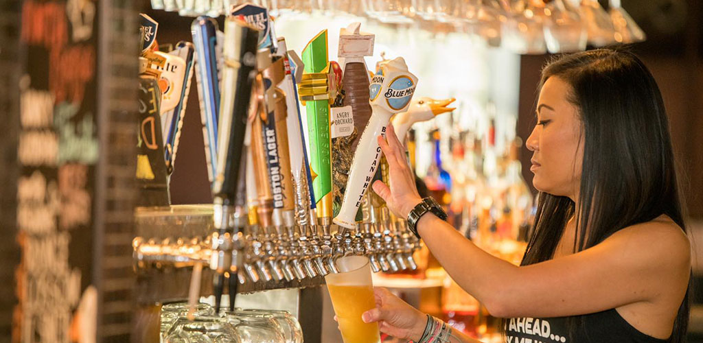 A woman getting beer on tap from Bar Louie