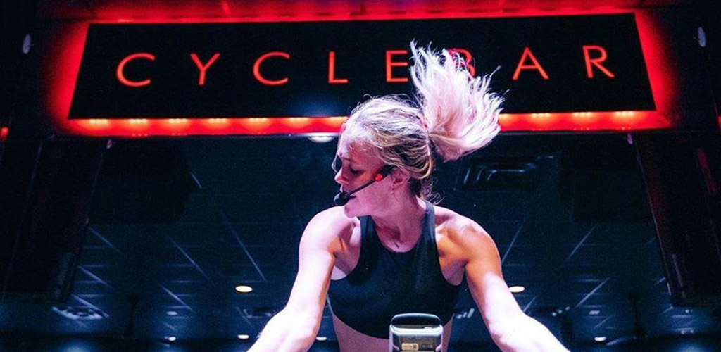 A hot woman in an intense cycling workout at Cycle Bar