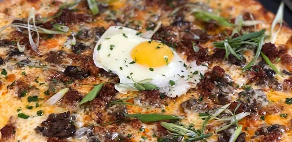 Pizza topped with an egg from Pharmacy