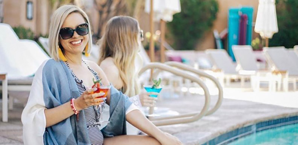 Fashionable ladies having cocktails by the pool at Royal Palms Resort and Spa