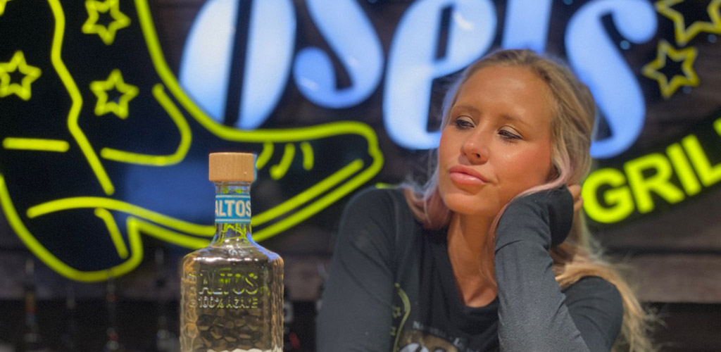 A hot woman with a bottle of tequila at Losers