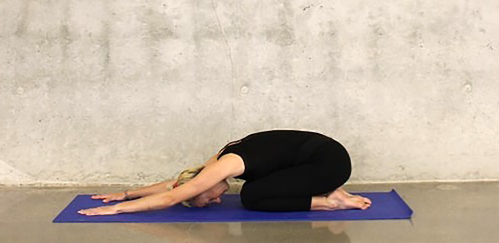 A fit woman in Balasana pose at Willow St. Yoga