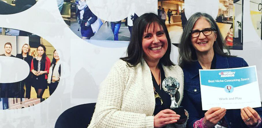 Two women holding awards won by Work and Play