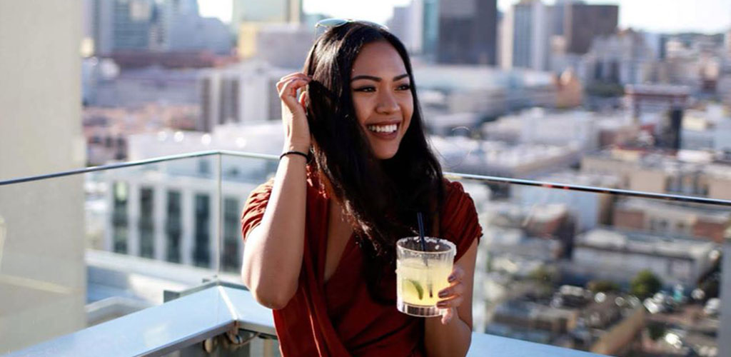 A beautiful woman holding a drink at the patio of ALTITUDE Sky Lounge