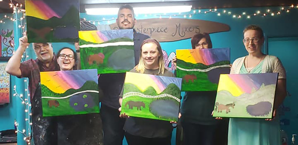 Friends showing off their paintings at Masterpiece Mixers