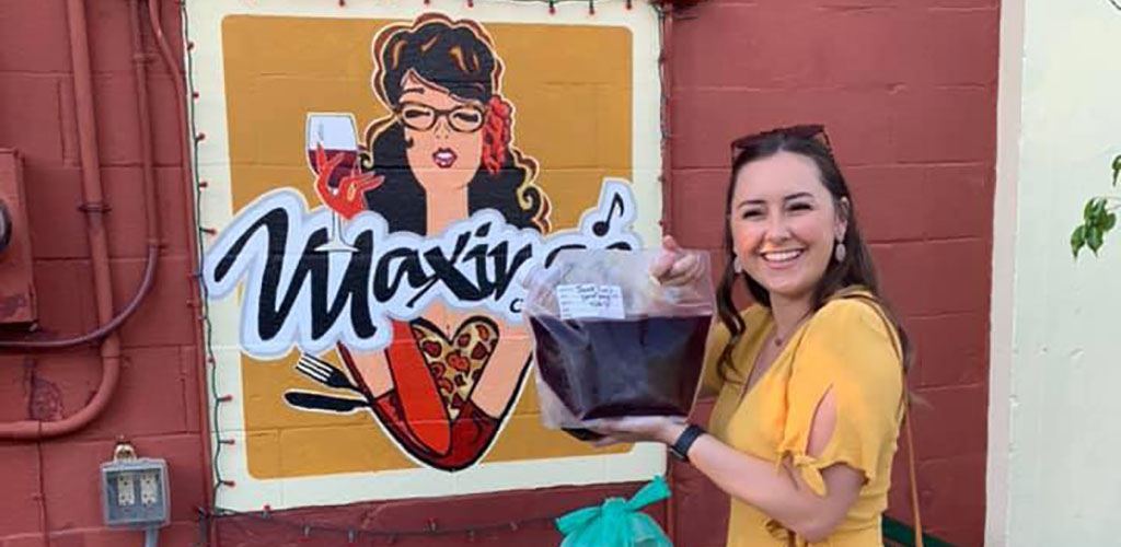 A pretty woman holding a bag of wine from Maxine's