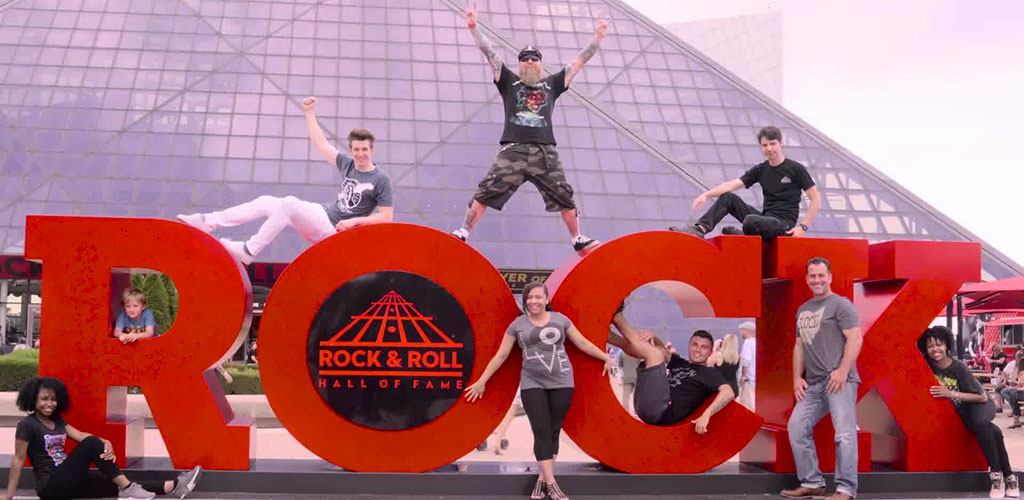 A group of friends posing in front of the Rock and Roll Hall of Fame