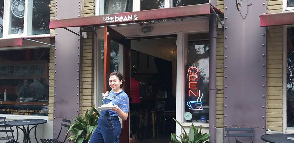 A woman smiling near the entrance of Sentient Bean