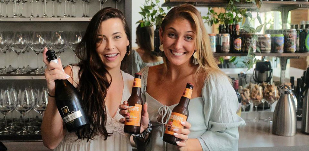 Two women holding beer bottles brewed by The Blind Monk